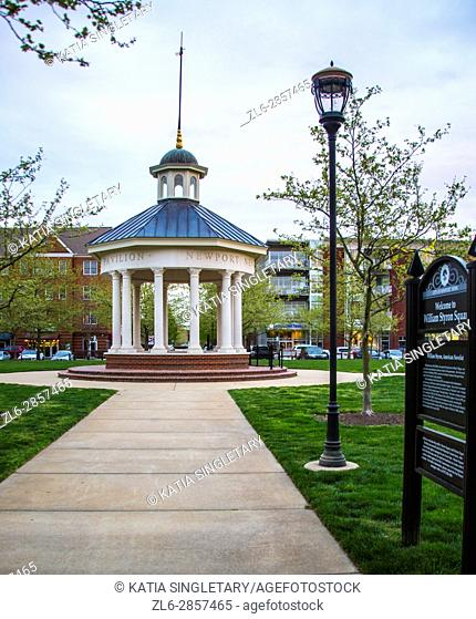 round beautiful Gazebo in a town square, in a town grass area where the sunset is setting