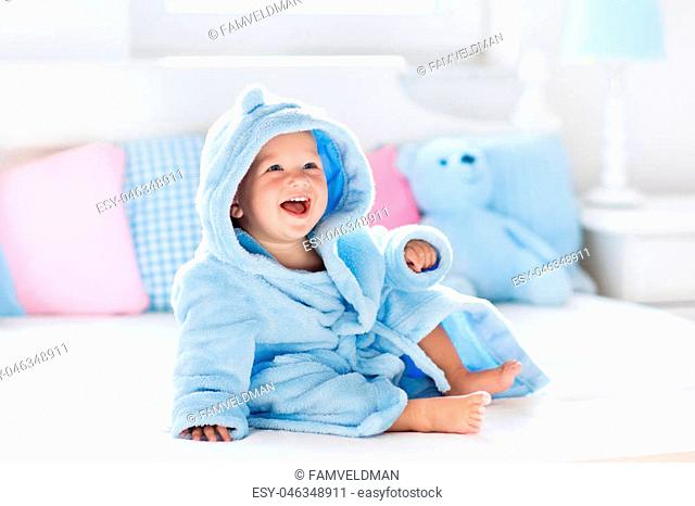 Cute happy laughing baby boy in soft bathrobe after bath playing on white bed with blue and pink pillows in sunny kids room