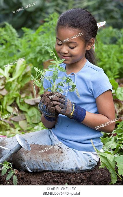 African girl holding plant in garden