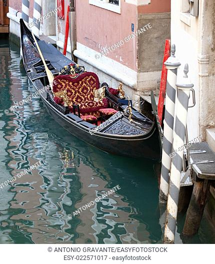Empty gondola parked in a narrow water canal