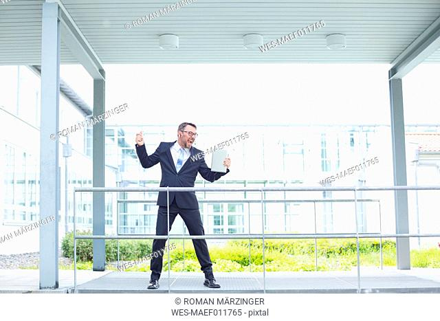 Enthusiastic businessman outside office building