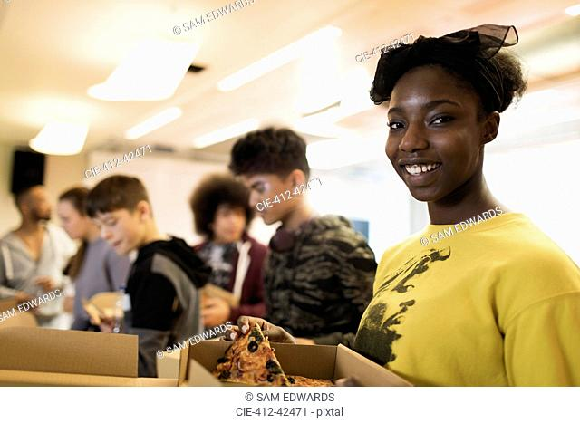 Portrait smiling teenage girl enjoying pizza with friends in community center