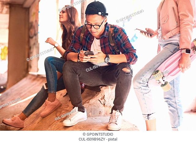Young skateboarding friends looking at smartphone at skateboard park