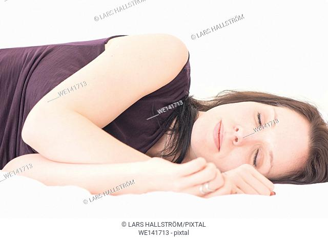 Sleeping woman. Portrait of young woman lying down in her bed with eyes closed, resting