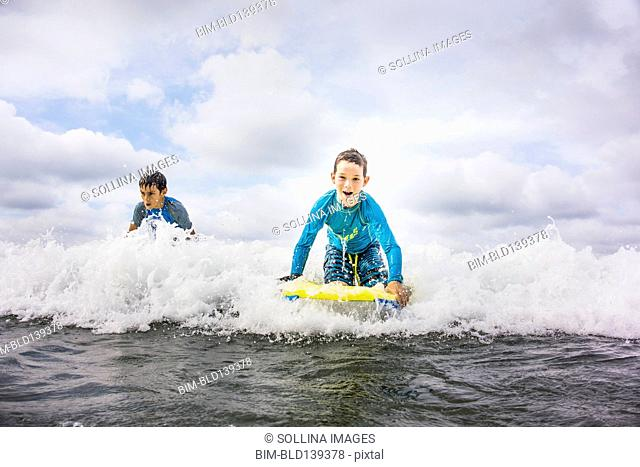 Boys surfing together in waves