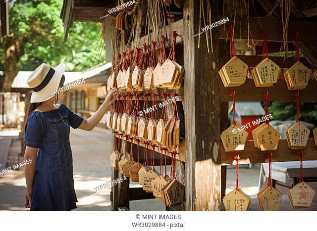 Young woman wearing blue dress looking at wooden fortune telling plaques at Shinto Sakurai Shrine, Fukuoka, Japan