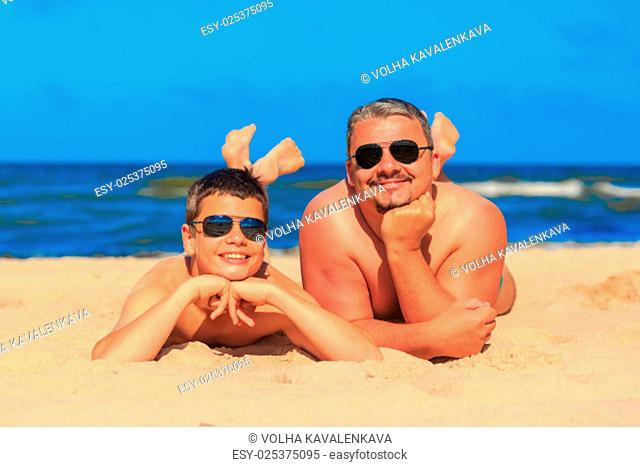 Happy laughing boy of thirteen and man of forty years ?? glasses on the sea beach. Shallow depth of field, focus on face