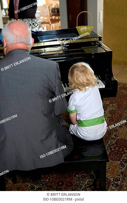 Young boy plays piano with grandfather