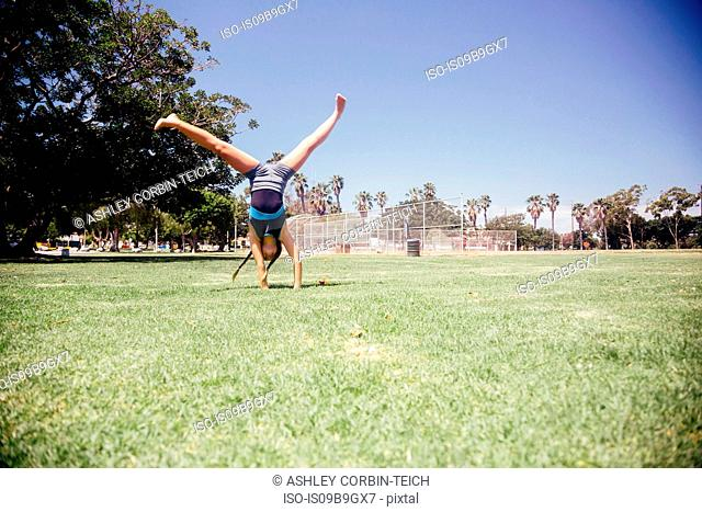 Schoolgirl doing cartwheel on school sports field