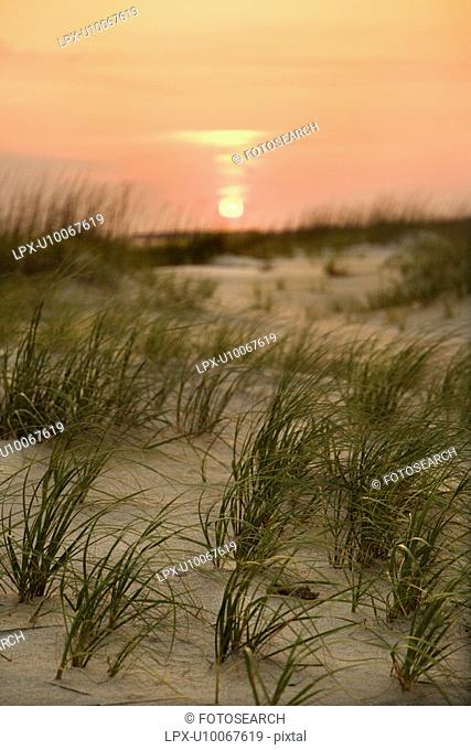 Sun setting over beach sand dune on Bald Head Island, North Carolina