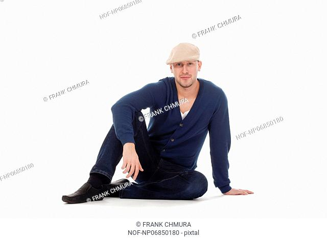 young handsome man with cap, sitting on the floor isolated on white