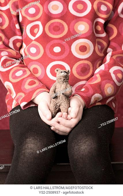 Portrait of little girl holding plastic toy bear in her hands