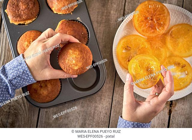Woman's hands garnishing muffins with candied orange slices