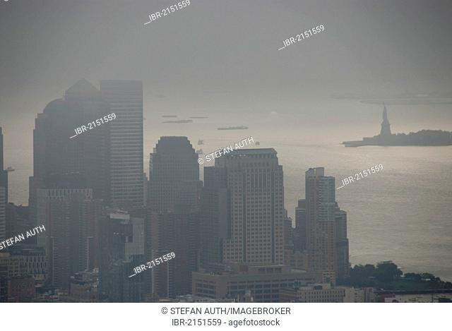 View from the Empire State Building over skyscrapers towards the Statue of Liberty in fog, mist-shrouded Financial District, gloomy, New York City, USA