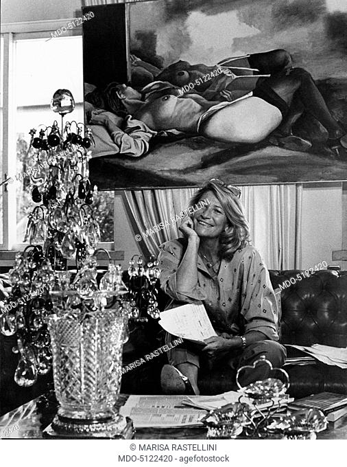 Italian fashion designer Marta Marzotto (Marta Vacondio) smiling while sitting on the sofa in her living room. She holds a pen and some sheets