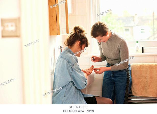 Friends applying nail varnish in bathroom