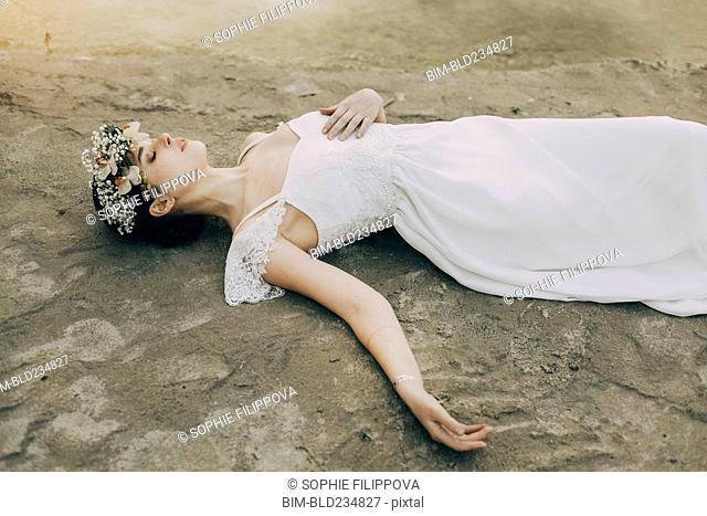 Caucasian bride laying on beach