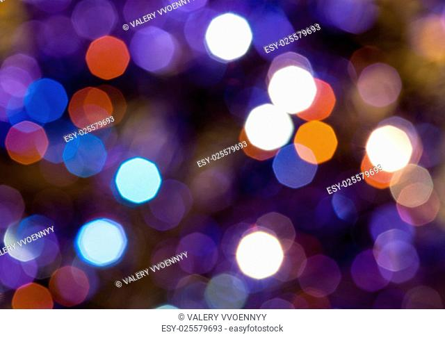 abstract blurred background - dark blue and violet flickering Christmas lights of electric garlands on Xmas tree