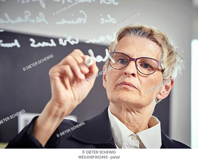 Portrait of woman writinging on glass pane in a classroom