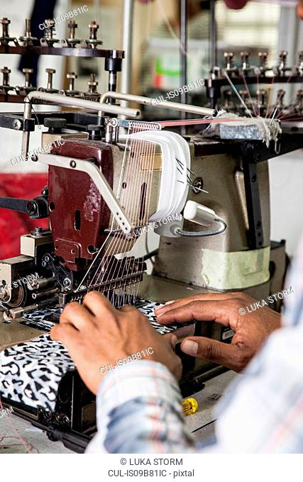 Person working on industrial smocking sewing machine in factory, Cape Town, South Africa