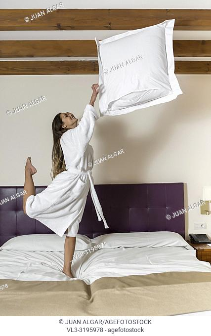 Smiling female jumping in bathrobe on bed and throwing up pillow in hotel room