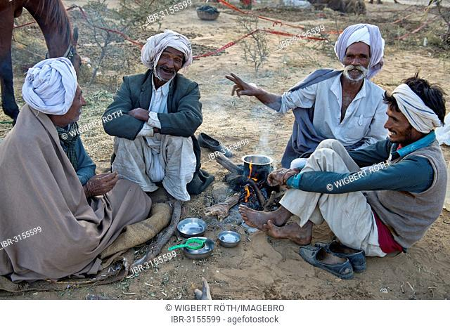 Four Indian men in turbans sitting on the ground having a conversation, milk tea is being prepared over an open fire, Pushkar Camel Fair