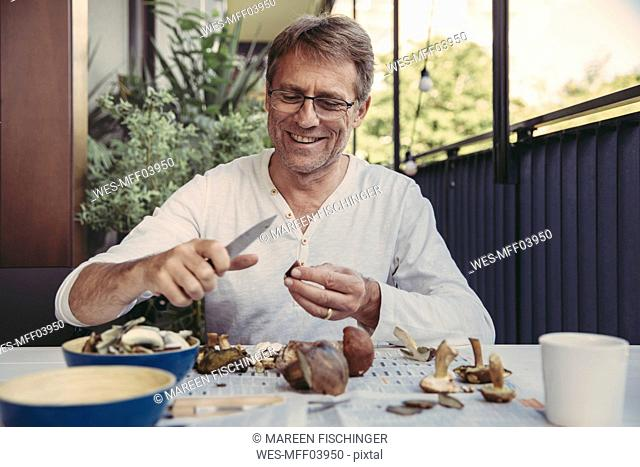 Portrait of happy man slicing orange bolete