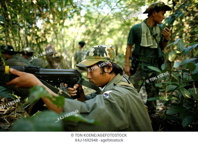 A KNLA soldier takes aim in the jungle around La Per Her In Myanmar Burma, thousands of people have settled near the border as a result of oppression in their...
