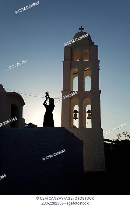 Silhouette of a woman taking photo near the Panagia Kimissis church situated at the cliff in Hora, Folegandros, Cyclades Islands, Greek Islands, Greece, Europe