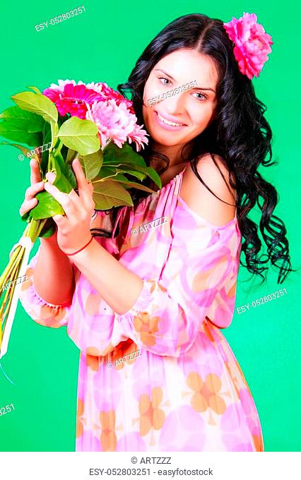 Spring portrait of a pretty young brunette with a bunch of gerberas over green background