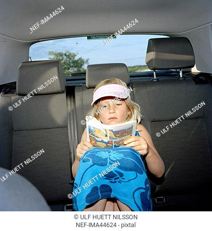Scandinavian girl sitting in the backseat reading a comic paper, Oland, Sweden