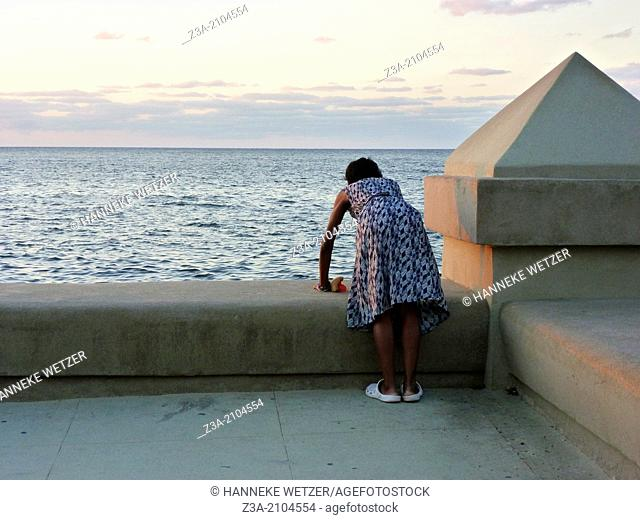 Bend Over Woman Watching Over The Sea, Havana, Cuba
