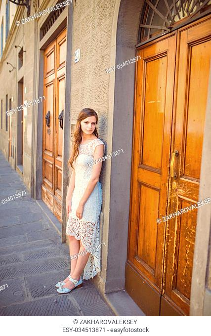young woman wearing a brown door outfit next to an old building