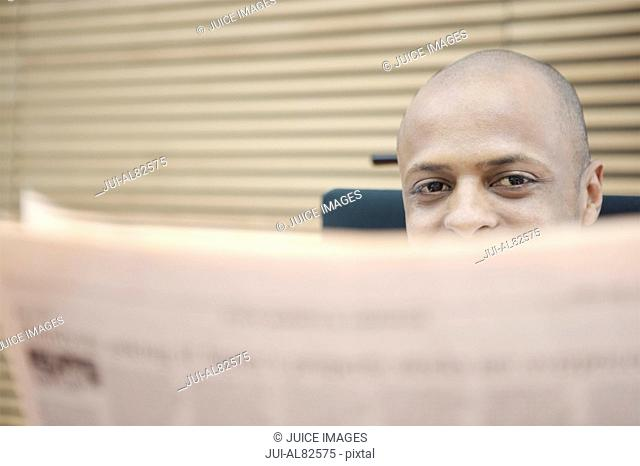 African man reading newspaper indoors