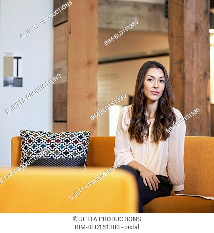 Mixed race businesswoman smiling on sofa
