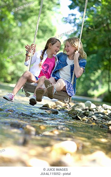 Two young girls on swing over river