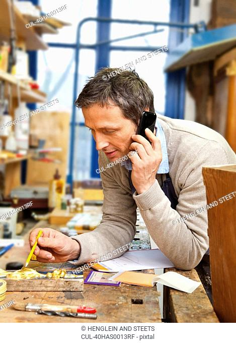 Carpenter talking on phone in shop