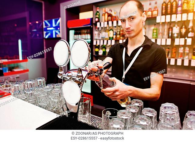 Bartender pours a beer at the bar in the club