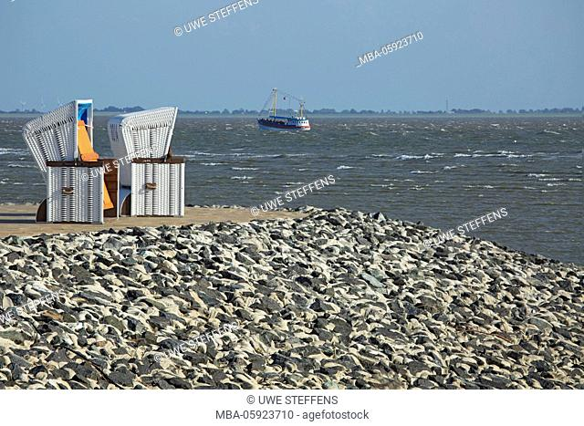 Beach chairs on the fixed dyke of North Sea in front of Büsum