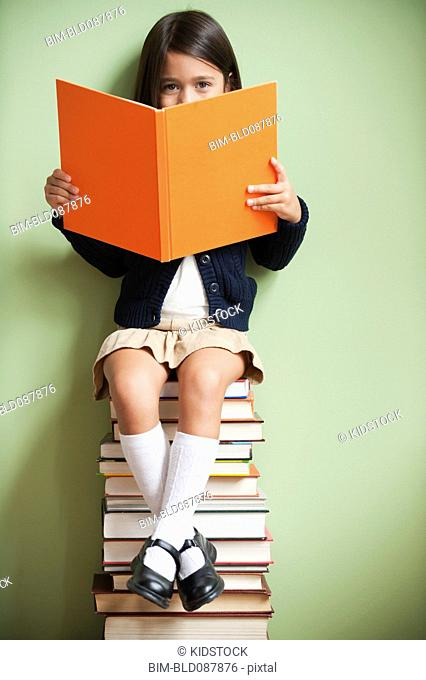 Mixed race girl sitting on stack of books reading book
