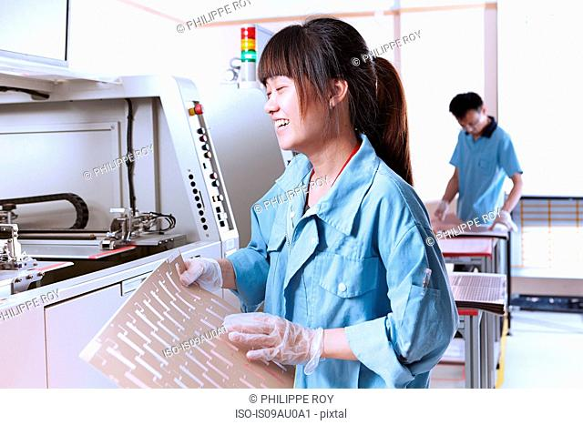 Young woman in manufacturing plant making flexible electronics eyes closed laughing