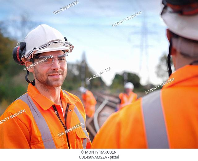 Portrait of apprentice railway maintenance worker in discussion on track