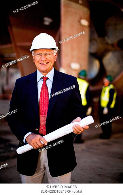 Businessman with blueprints on dry dock