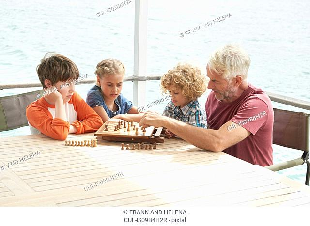 Grandfather and grandchildren playing chess
