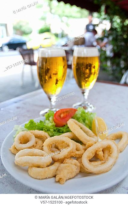 Fried squids serving and two glasses of beer in a terrace. Madrid, Spain