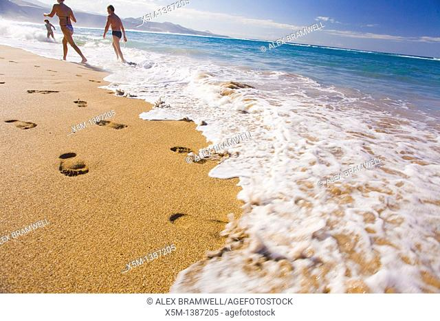 Footprints and people on Las Canteras beach as a wave breaks on the shore