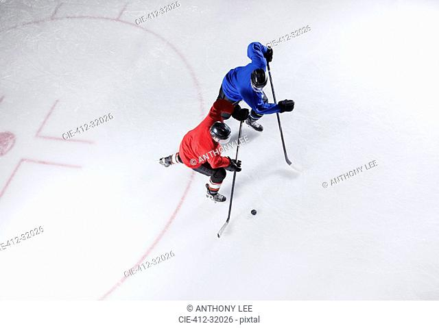Hockey players going for the puck on ice