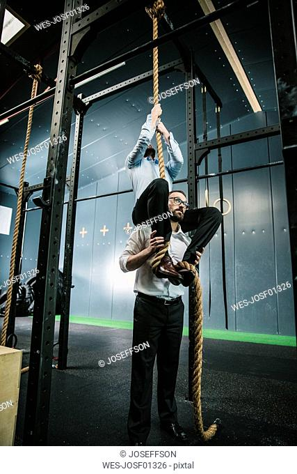 Businessman supporting colleague, climbing a rope