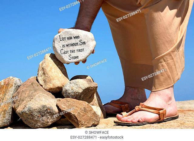A man holds a white rock inscribed with a bible verse from John 8:7 - Let him who is without sin cast the first stone. Closeup. Focus to rock