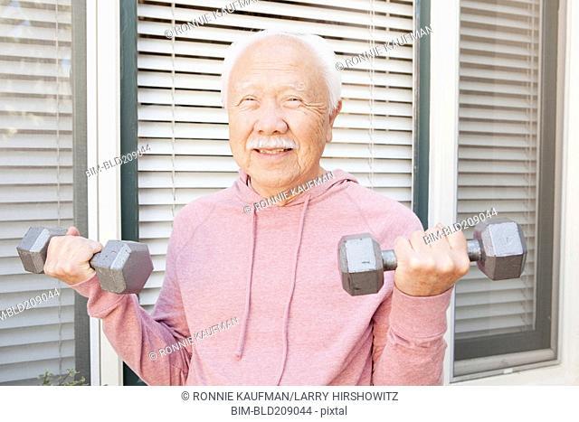 Older Asian man lifting weights outdoors